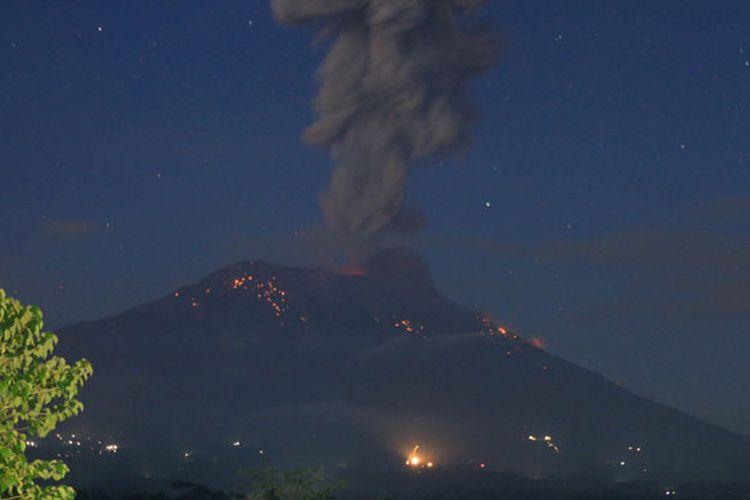 Abu vulkanis dan batu pijar terlontar dari kawah Gunung Agung saat erupsi yang terpantau dari Pos Pengamatan Gunung Api Agung, Karangasem, Bali, Minggu (21/4/2019). Gunung Agung yang berstatus siaga itu kembali erupsi pada pukul 18.56 WITA dengan melontarkan abu vulkanis mencapai ketinggian 3.000 meter dari kawah yang disertai lontaran batu pijar ke lereng gunung tersebut.