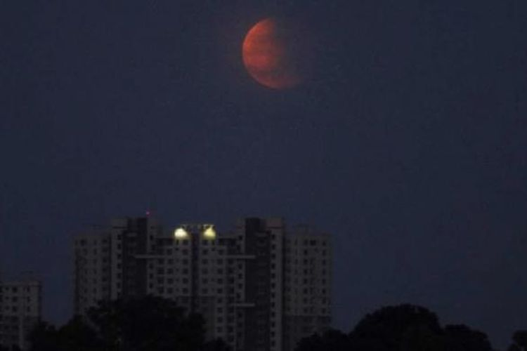 Gerhana bulan terlihat di Bhubaneswar, India, 8 Oktober 2014. Warna merah pada gerhana bulan dipengaruhi oleh pembiasan atmosfer Bumi, disebut dengan bulan merah darah.