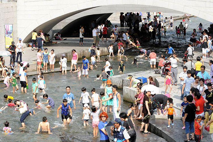 Warga Korea Selatan menikmati kesejukan di aliran Cheonggyecheon di tengah teriknya musim panas.