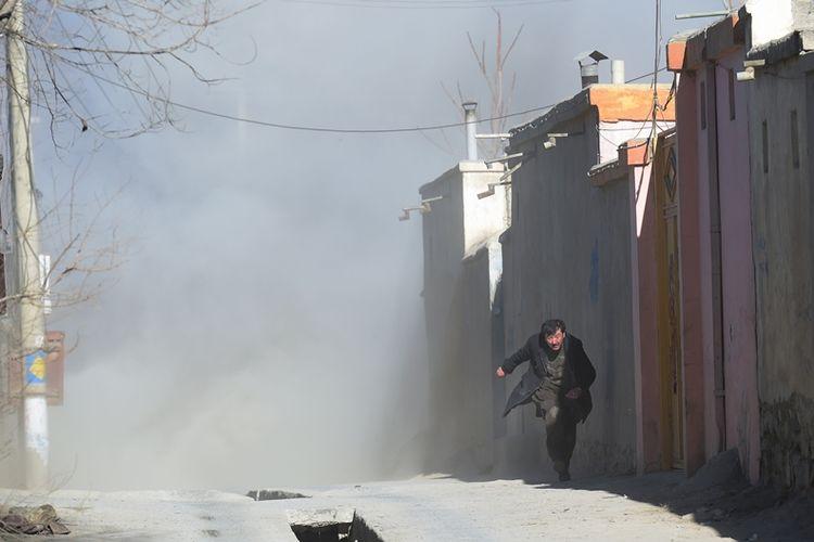 Seorang pria Afghanistan melarikan diri setelah ledakan ketiga di sebuah pusat kebudayaan Syiah di Kabul, Afganistan, Kamis (29/12/2017). (AFP/Shah Marai)