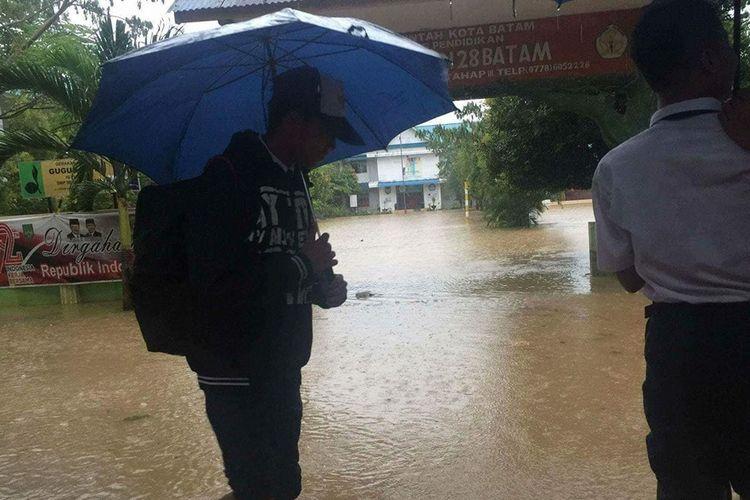 Salah seorang siswa SMPN 28 Batam Kota mengurungkan niatnya ke sekolah. Saat ini SMPN 28 terendam banjir akibat hujan deras yang mengguyur Kota Batam sejak Senin malam kemarin.