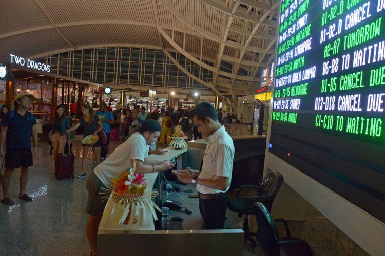Calon penumpang menunggu jadwal penerbangan di Bandara Ngurah Rai Bali, Sabtu (25/11/2017) malam. Sebanyak 17 jadwal penerbangan internasional dari dan menuju Bali dibatalkan karena dampak erupsi Gunung Agung.