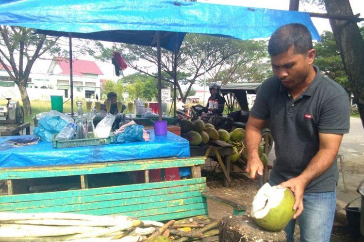 Pedagang mengupas kelapa muda di Jalan Lingkar Stadion Tunas Bangsa, Kota Lhokseumawe, Aceh, Minggu (7/1/2018).