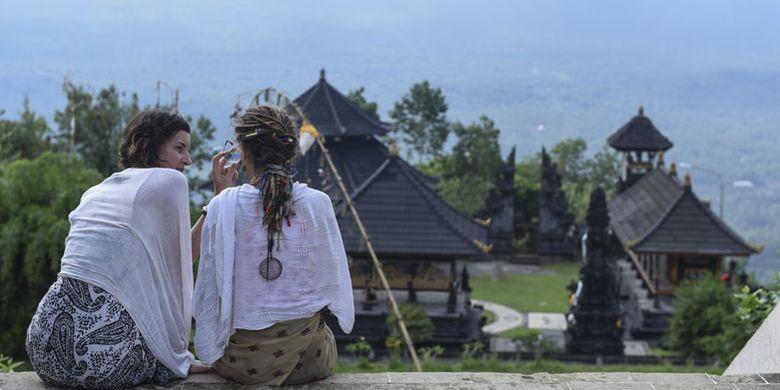 Wisatawan asing berada di Pura Lempuyang, Karangasem, Bali, Kamis (7/12/2017). Menteri Pariwisata Arief Yahya menyatakan pemerintah memangkas target kunjungan wisatawan mancanegara pada tahun ini dari 15 juta menjadi 14 juta wisatawan akibat erupsi Gunung Agung di Bali.