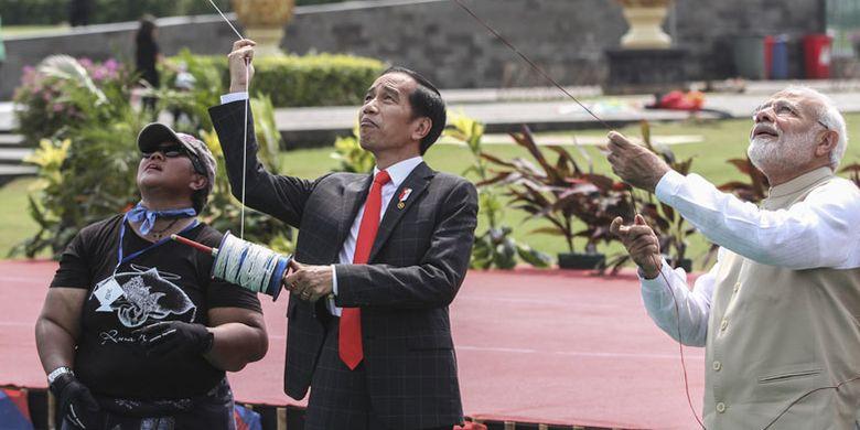 Presiden Joko Widodo (tengah) bersama Perdana Menteri (PM) India Narendra Modi (kanan) bermain layang-layang saat menghadiri Pameran Layang-Layang Indonesia-India di kawasan Monas, Jakarta, Rabu (30/5/2018). Pada kunjungan resmi pertama PM India ke Indonesia Presiden Joko Widodo mengajak untuk bermain dan menghadiri pameran layang-layang yang merupakan permainan tradisional populer di Indonesia dan India.
