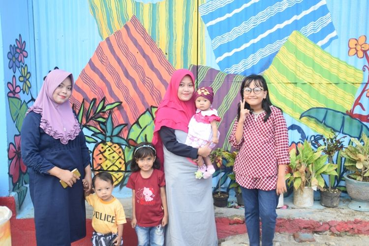Para pengunjung berfoto dengan latar belakang Kampung Tenun Warna Warni di Kampung Sulaa, Baubau, Sulawesi Tenggara.