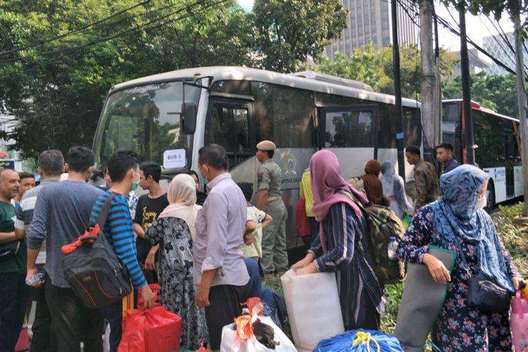 Para pencari suaka yang sudah berhari-hari menetap di trotoar Jalan Kebon Sirih, Jakarta Pusat, bersiap-siap untuk dipindahkan ke Lapangan Eks Kodim di Kalideres, Jakarta Barat, Kamis (11/7/2019).