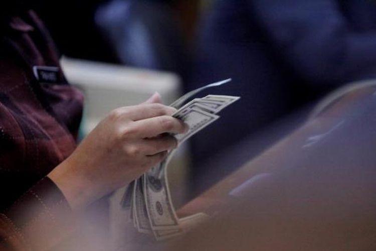 Petugas memeriksa kondisi lembaran Dollar AS yang akan dijual di tempat penukaran valuta asing.