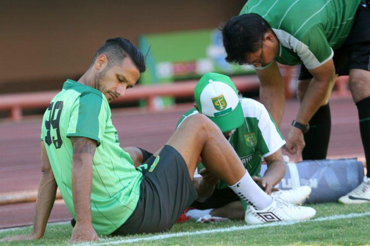 Gelandang Persebaya, Raphael Maitimo, saat menjalani perawatan oleh fisioterapis pada sesi latihan tim di Stadion Jenggolo, Sidoarjo, Kamis (2/8/2018).