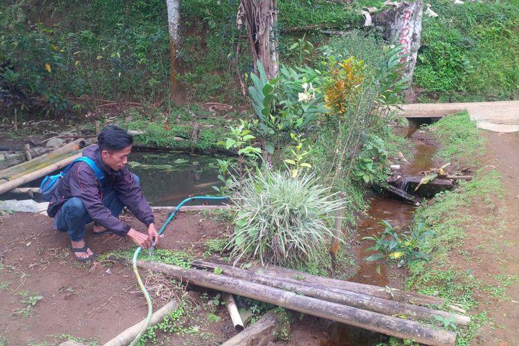 Seorang warga memperbaiki selang pipa air di Kampung Pasir Tengah, Desa GedePangrango, Kadudampit, Sukabumi, Jawa Barat, Rabu (13/6/2018).