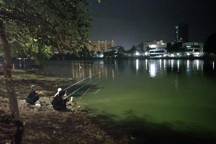 Masyarakat melakukan kegiatan memancing sembarimenyambut kedatangan tahun 2018 di tepi Danau Sunter, Jakarta Utara, Minggu (31/12/2017).