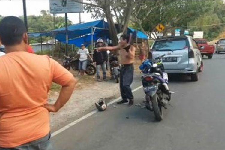 Keberatan ditilang polisi, seorang pengendara sepeda motor di Kota Mamuju, Sulawesi Barat, mengamuk sabil banting helem dan membuka baju di jalan raya.