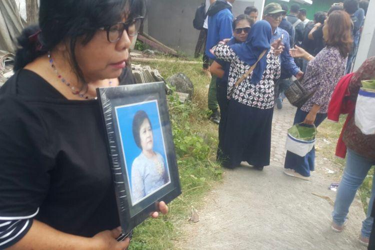 Rekan satu gereja almarhumah Sri Pudjiastuti memegang foto korban di lokasi pemakaman korban bom teroris Gereja Pantekosta Pusat Surabaya di TPU Bonoloyo, Kadipiro, Kota Solo, Jawa Tengah, Selasa ( 15 / 5 / 2018) siang.