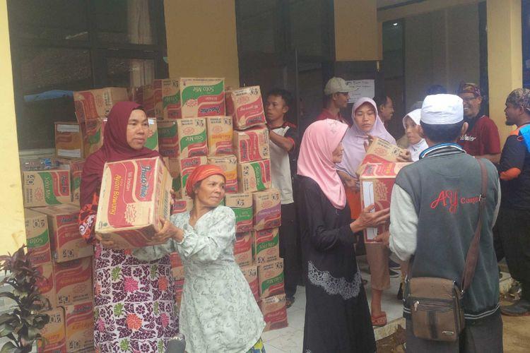 Sejumlah ibu-ibu ikut bergotongroyong menurunkan dus mi instan kiriman dari donatur di Posko Penanggulangan Bencana Alam di Dusun Cimapag, Desa Sirnaresmi, Kecamatan Cisolok, Sukabumi, Jawa Barat, Kamis (10/1/2019).