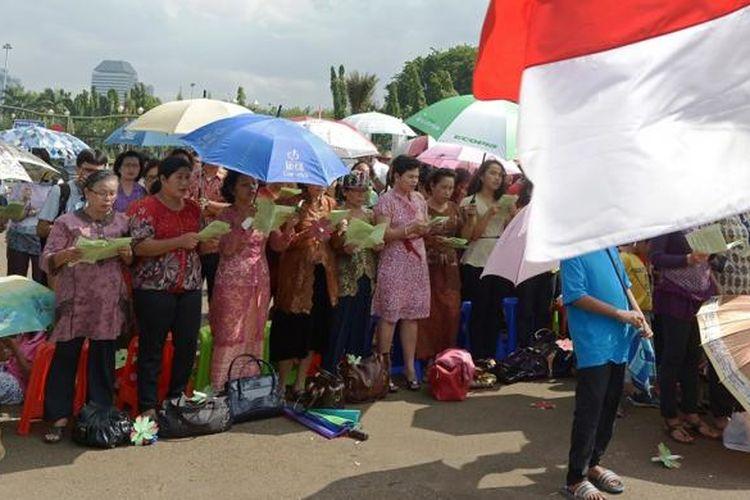 Meski terik dan sempat turun hujan, jemaat Gereja Yasmin dan HKBP Filadelfia tetap melaksanakan ibadah di seberang Istana Merdeka, Jakarta, Rabu (25/12/2013). Mereka memprotes kasus pembangunan gereja yang tak kunjung selesai.