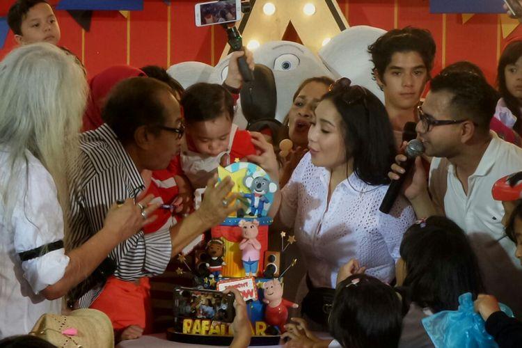 Rafathar dikelilingi keluarganya saat tiup lilin di Club House Green Andara, Depok, Jawa Barat, Minggu (20/8/2017).