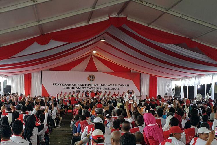 Presiden Joko Widodo menyerahkan sertifikat hak atas tanah kepada Gubernur DKI Jakarta Djarot Saiful Hidayat dan 13 perwakilan warga dalam acara penyerahan sertifikat hak atas tanah di Lapangan Park & Ride Jalan MH Thamrin, Jakarta Pusat, Minggu (20/8/2017).