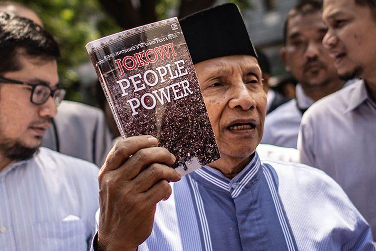 Ketua Dewan Kehormatan Partai Amanat Nasional (PAN)  Amien Rais (tengah) menunjukkan buku berjudul Jokowi People Power saat jeda pemeriksaan untuk Shalat Jumat di Direktorat Reserse Kriminal Umum (Ditreskrimum) Polda Metro Jaya, Jakarta, Jumat (24/5/2019). Amien Rais diperiksa sebagai saksi atas kasus dugaan makar dengan tersangka Eggi Sudjana.