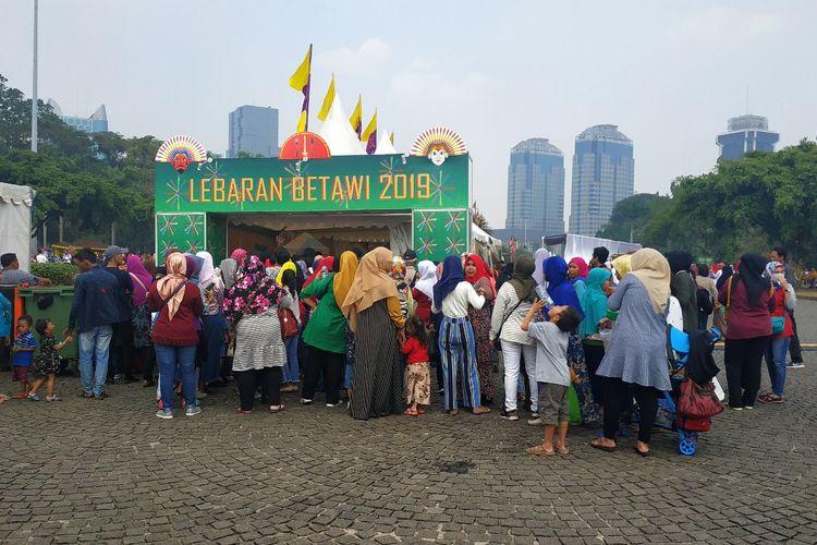 Pengunjung acara Lebaran Betawi 2019 di Monas berjejalan mengantre masuk ke stan makanan Betawi gratis, Sabtu (20/7/2019).