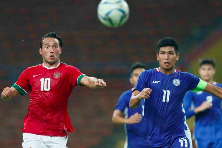 Penyerang timnas Indonesia, Ezra Walian, mencoba mengejar bola dan lepas dari kawalan kapten Filipina pada pertandingan Grup SEA Games 2017 di Shah Alam, Kamis (17/8/2017).