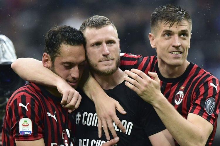 Hakan Calhanoglu dan Krzysztof Piatek merangkul Ignazio Abate yang memainkan pertandingan terakhirnya bersama AC Milan seusai laga versus Frosinone di San Siro, 19 Mei 2019.