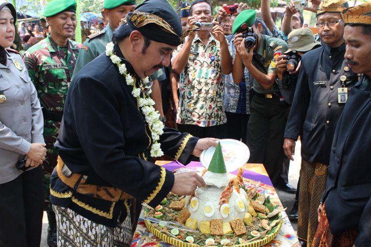Bupati Tegal Enthus Susmono memotong tumpeng, Kamis (6/11).   *** Local Caption *** Bupati Tegal, Enthus Susmono memotong tumpeng, dalam acara Ruwat Bumi Obyek Wisata Pantai Purwahamba Indah di Kabupaten Tegal, Jawa Tengah, Kamis (6/11). Ruwat bumi yang merupakan tradisi tahunan tersebut dimaksudkan sebagai wujud syukur terhadap keberlangsungan kehidupan pada obyek wisata, sekaligus sebagai upaya merawat keberadaan bahasa Tegal, yang digunakan sebagai bahasa pengantar dalam kegiatan ruwat bumi.