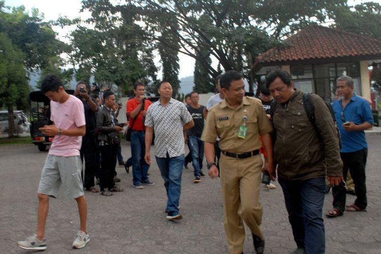 Sekretaris Disnakertrans Kabupaten Sukabumi, Ali Iskandar (Kanan kedua) bersama enam WNA Cina saat tiba di Kantor Imigrasi Sukabum di Jalan Lingkar Selatan, Sukabumi, Jawa Barat, Senin (23/10/2017).