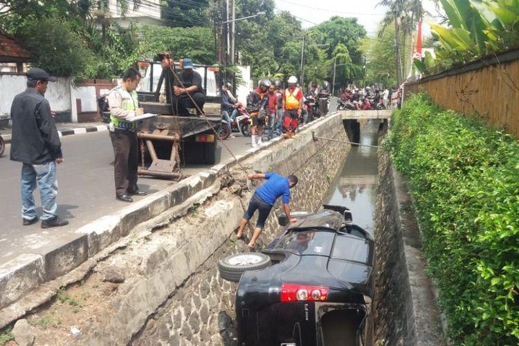 Sebuah mobil Daihatsu Xenia terperosok di Jalan Darmawangsa, Jakarta Selatan, Sabtu (8/9/2018)