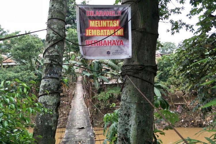 Jembatan gantung Indiana Jones di RT 011 RW 002 Kelurahan Srengseng Sawah, Jagakarsa, Jakarta Selatan, dipasangi spanduk larangan untuk dilintasi. Jembatan ini tidak akan dibangun dengan jembatan baru yang permanen. Foto diambil Selasa (13/3/2018).