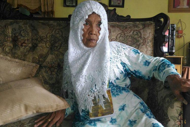 Sitti Bunayya dengan pandangan kosong sambil mengenakan jilbab yang rencananya akan dipakai saat beribadah umrah.
