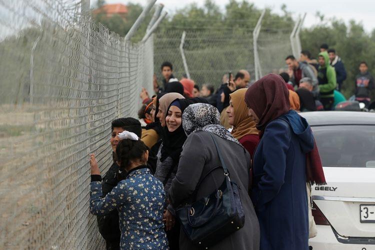 Sekelompok perempuan menonton pertandingan sepak bola dari balik pagar di stadion kamp pengungsi Nuseirat, Jalur Gaza, Minggu (28/1/2018).