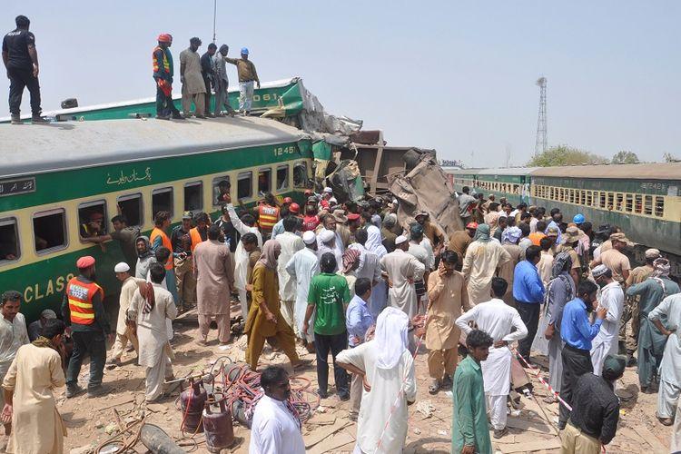 Warga bersama petugas penyelamat berusaha menyelamatkan penumpang dalam kecelakaan kereta api yang terjadi di Pakistan, pada Kamis (11/7/2019).