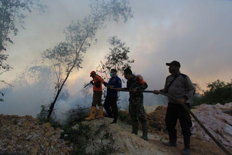 Sejumlah petugas Badan Penanggulangan Bencana Daerah (BPBD), Babinsa, dan kepolisian berupaya memadamkan kebakaran hutan dan lahan dekat pemukiman warga, di kecamatan Dumai Barat, kota Dumai, Dumai, Riau, Selasa (12/2/2019). Kebakaran hutan dan lahan yang terjadi di sejumlah daerah di pesisir Riau semakin meluas akibat cuaca panas. ANTARA FOTO/Aswaddy Hamid