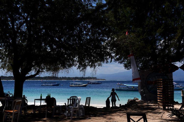 Seorang WNA memungut sampah plastik yang berhamburan di pinggir pantai di Gili Trawangan, Lombok Utara, NTB, Kamis (9/8). Kondisi pulau wisata tersebut sepi pascagempa yang terjadi pada 5 Agustus lalu,  meski sejumlah WNA dan warga lokal masih bertahan di pulau itu. ANTARA FOTO/Zabur Karuru/aww/18.