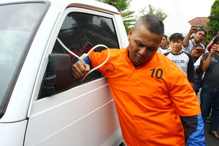 Pelaku spesialis pecah kaca yang juga Finalis Indonesia Idol 2008 Dede Richo (tengah) memperagakan cara melakukan aksi pencurian dengan modus pecah kaca saat pers rilis di Mapolsek Serpong, Serpong, Tangerang Selatan, Rabu (19/9/2018). Alasan kebutuhan ekonomi yang menyebabkan Dede Richo beralih profesi menjadi pencuri dibantu sang adik DFO alias Bryan, dan menurut pengakuannya dirinya sudah sepuluh kali melakukan aksi pecah kaca mobil di kawasan Serpong.