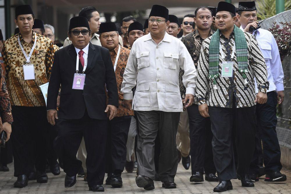 Calon Presiden nomor urut 2 Prabowo Subianto (tengah) didampingi Ketua Umum Lembaga Dakwah Islam Indonesia (LDII) Abdullah Syam (kedua kiri) dan Pimpinan Pondok Pesantren Minhaajurrosyidiin Asy'ari Akbar (kanan) tiba di lokasi Rakernas LDII di Jakarta, Kamis (11/10/2018). Rapat kerja tersebut mengangkat tema