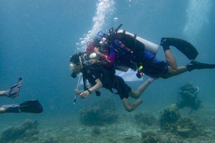Suasana pengibaran bendera di bawah laut oleh penyandang disabilitas.