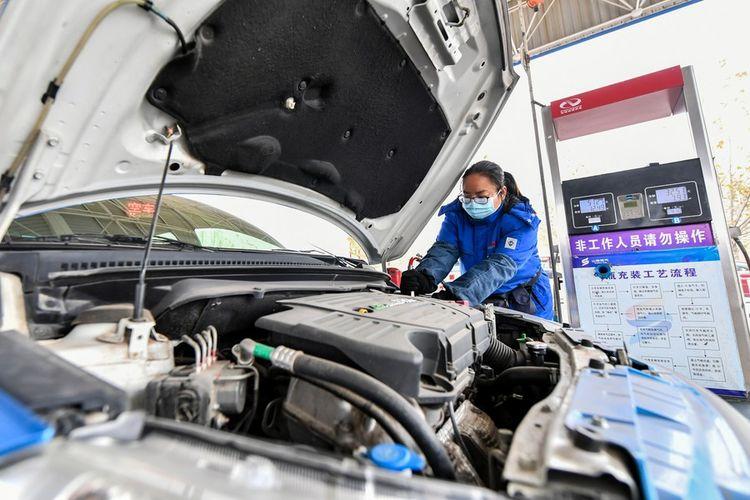 Foto menunjukkan seorang pekerja sedang mengisi bahan bakar sebuah mobil dengan gas batu bara (coal seam gas) di stasiun pengisian bahan bakar di kota Jincheng, provinsi Shanxi, China utara, pada 9 Desember 2020. Para personel yang melakukan kontak langsung dengan barang-barang itu telah dikarantina dan semua tes mereka dinyatakan negatif Covid-19. Barang-barang tersebut juga telah disegel.