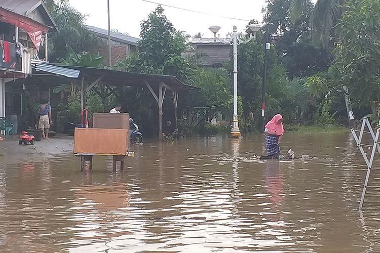 Warga mengeluarkan sampah dari rumahnya akibat diseret banjir di Kota Pasir Pengaraian, Kabupaten Rohul, Riau, Rabu (27/11/2019).