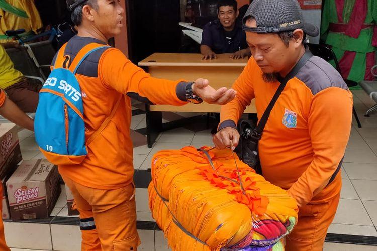 Petugas PPSU Kelurahan Kembangan Selatan sibuk menurunkan bantuan logistik di Kompleks Puri Indah, Jakarta Barat, Kamis (2/1/2020) siang.