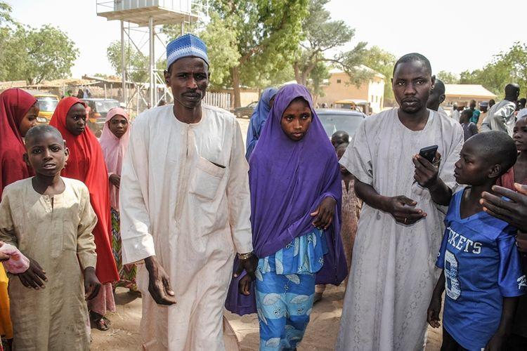 Seorang gadis yang dibebaskan oleh Boko Haram berjalan dengan ayahnya (kiri) di Dapchi, Nigeria, rabu (21/3/2018). (AFP)