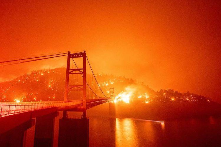Suasana Jembatan Bidwell Bar yang dikelilingi oleh api di kawasan Danau Oroville, saat terjadi kebakaran besar di Oroville, California, AS, Rabu (9/9/2020). Kebakaran terbesar dalam sejarah California itu dilaporkan telah menghancurkan 470 ribu hektar vegetasi kering dan 3,1 juta hektar lahan terbakar.