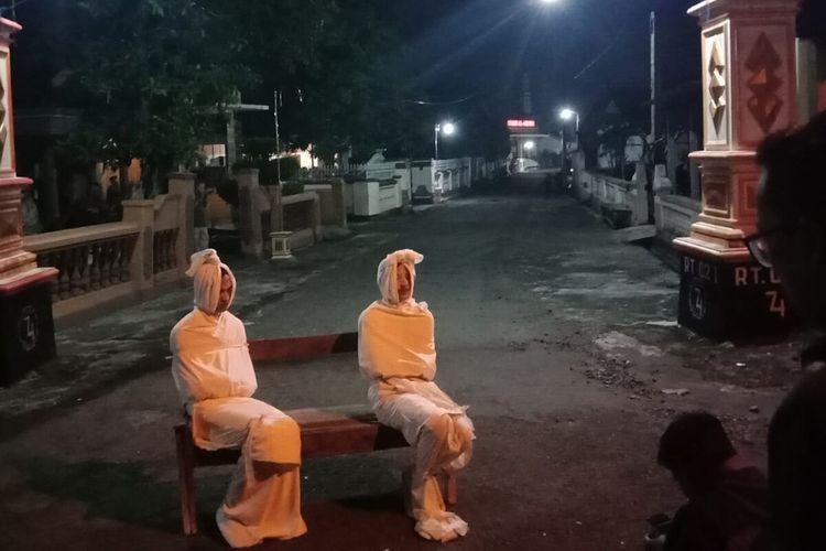 Warga Dukuh Kesongo RT 002, RW 001, Desa Kepuh, Kecamatan Nguter, Kabupaten Sukoharjo, Jawa Tengah, Rabu (1/4/2020) malam memakai kostum pocong. Mereka memakai koatum itu setelah foto dua pocong tahun 2019 silam yang diunggah viral di media sosial.