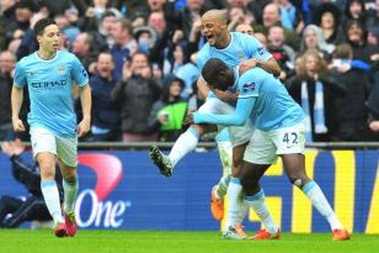 Kapten Manchester City, Vincent Kompany, merayakan gol rekannya, Yaya Toure, seusai membobol gawang Sunderland pada laga final Piala Liga Inggris di Stadion Wembley, Minggu (2/3/2014).