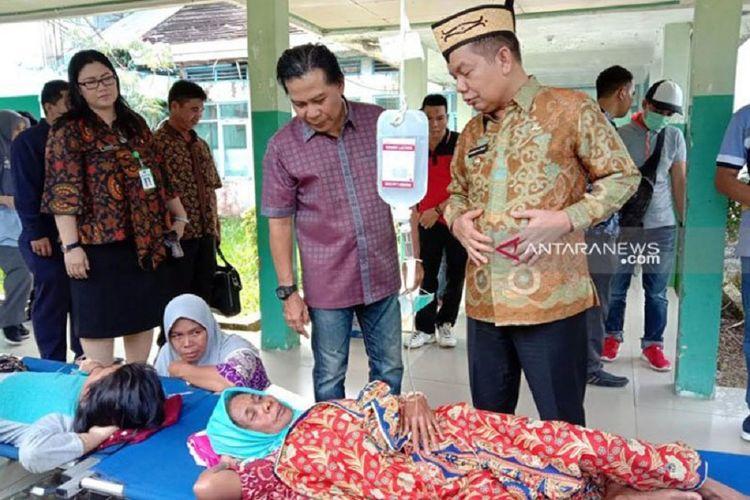 Bupati Kapuas Ben Brahim S Bahat (kanan) didampingi istri dan Ketua DPRD Kapuas Algrin Gasan meninjau para korban keracunan di RSUD dr Soemarno Sostroatmodjo Kuala Kapuas, Jumat (24/5/2019).