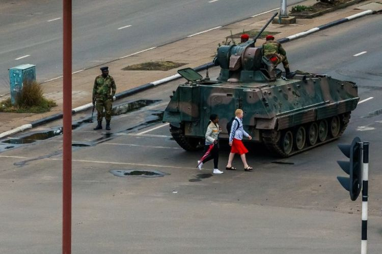 Warga kota Harare melintasi di belakang sebiuah tank AD Zimbabwe yang diparkir di salah satu ruas jalan kota tersebut, Rabu (15/11/2017).