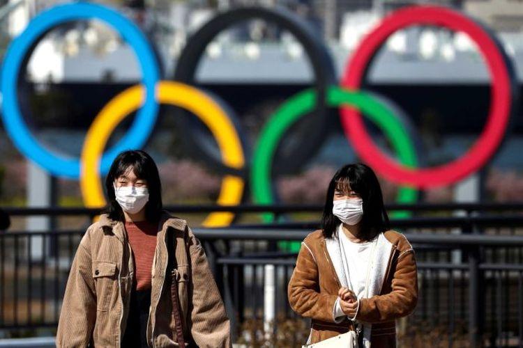 Dua warga berjalan di depan logo olimpiade di Tokyo, Jepang.