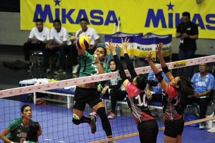 Pemain Jakarta Elektrik PLN, Aprilia Manganang (kedua dari kiri), melakukan smes ke arah sisi lapangan Jakarta Pertamina Energi pada laga seri pertama final four Proliga 2017 di GOR Sritex Arena, Solo, Minggu (9/4/2017).