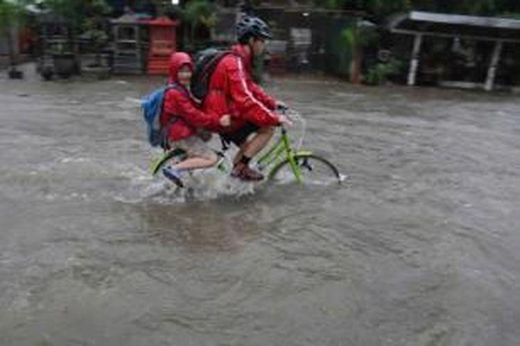 Pengendara sepeda menerobos banjir di Jalan Budi Jaya, Kebun Jeruk, Jakarta, Senin (9/2/2015). Curah hujan yang tinggi mengakibatkan sejumlah tempat di ibu kota terendam banjir.