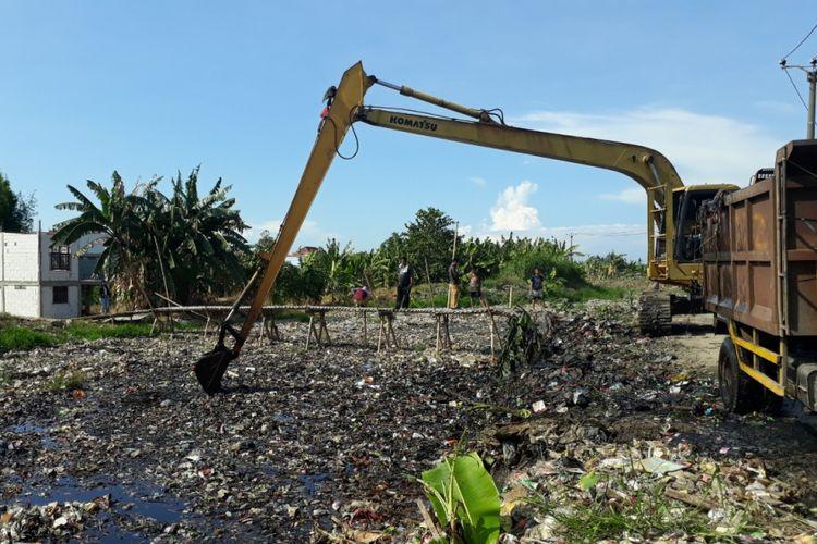 Alat berat angkut sampah di Kali Pisang Batu, Desa Pqhlawan Setia, Tarumajaya, Kabupaten Bekasi, Senin (7/1/2019).